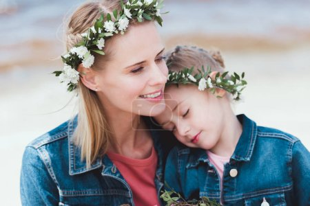 smiling mother and daughter in floral wreaths hugging on shore