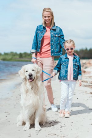 happy mom and kid walking with golden retriever dog on sea shore