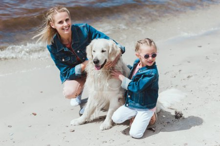 happy family with golden retriever dog on sea shore