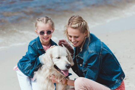 smiling family with golden retriever dog on sea shore