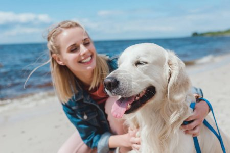 Photo pour Heureuse femme attrayante assis avec chien golden retriever sur le rivage de la mer - image libre de droit
