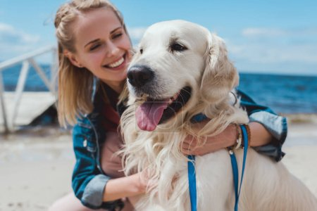 smiling blonde woman sitting with friendly dog on sea shore