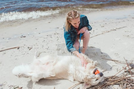 smiling woman playing ball with golden retriever dog on shore