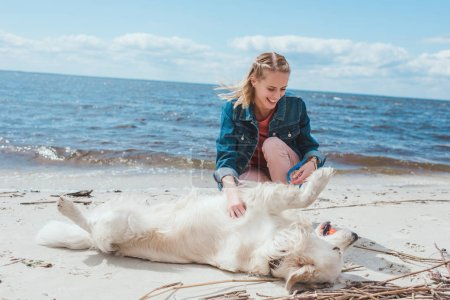 attractive happy woman playing ball with golden retriever dog on sea shore