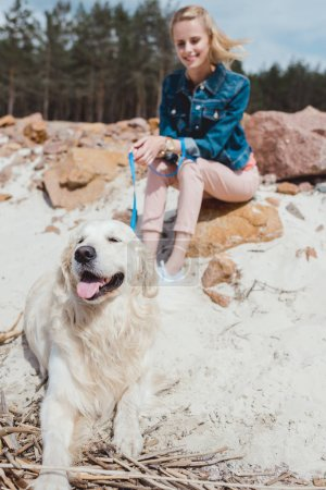 selective focus of woman with golden retriever dog on shore