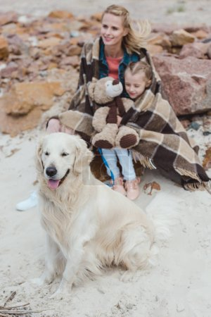 mom and daughter in blanket sitting with dog on shore