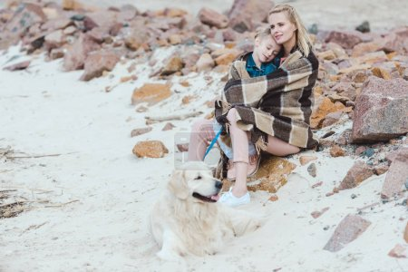 beautiful mother and sleeping kid in blanket sitting with dog on shore
