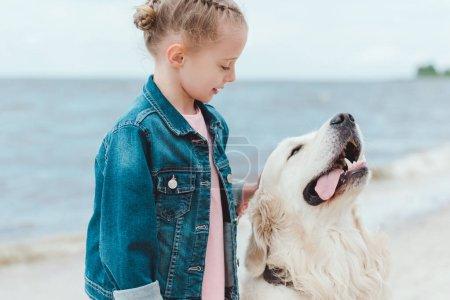 adorable child with friendly golden retriever dog on sea shore