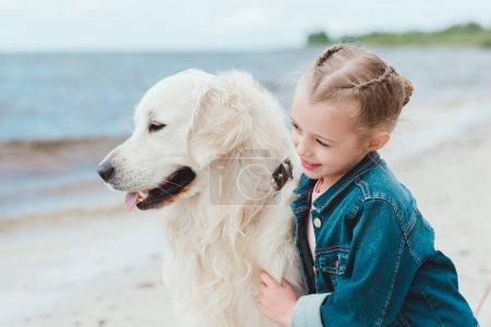 adorable kid hugging golden retriever dog on sea shore