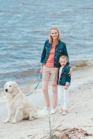 beautiful family walking with golden retriever dog near the sea
