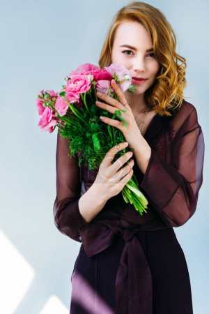 beautiful elegant girl holding pink flowers and looking at camera isolated on grey