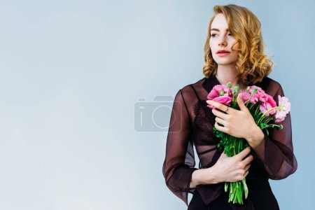 beautiful young woman holding tender pink flowers and looking away isolated on grey