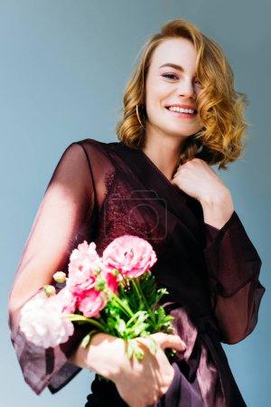 Foto de Vista de ángulo bajo de hermosa chica sosteniendo flores y sonriendo a cámara aislada en gris - Imagen libre de derechos