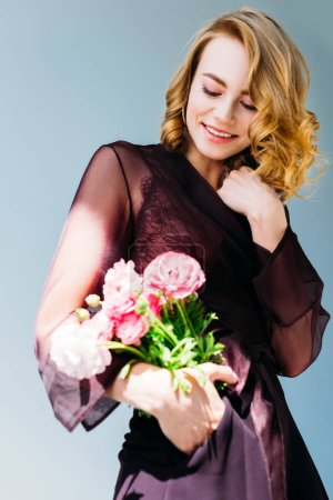low angle view of beautiful smiling girl holding pink flowers isolated on grey