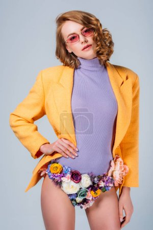 beautiful young woman in sunglasses and panties made of flowers looking at camera isolated on grey