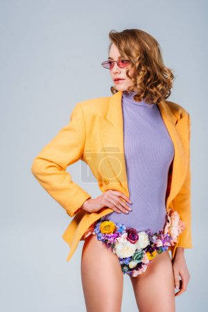 girl in sunglasses and panties made of flowers standing with hand on waist and looking away isolated on grey