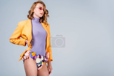 stylish girl in sunglasses and panties made of flowers standing with hand on waist isolated on grey