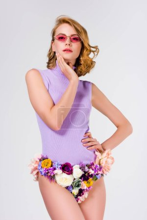 beautiful woman in sunglasses and panties made of flowers standing with hand on hip and looking at camera isolated on grey