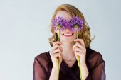 beautiful happy young woman holding bright purple flowers isolated on grey