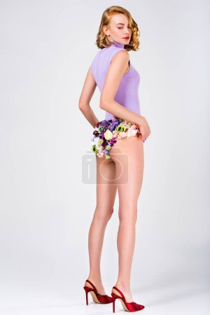 side view of beautiful girl in panties made of flowers and high heeled shoes posing on grey