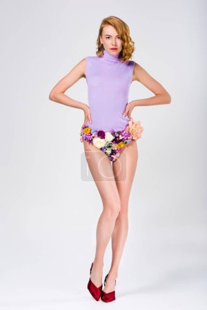 full length view of beautiful girl in panties made of flowers and high heeled shoes standing with hands on waist and looking at camera on grey
