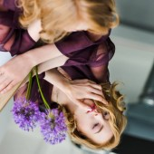 selective focus of girl looking at reflection while lying on mirror with purple flowers