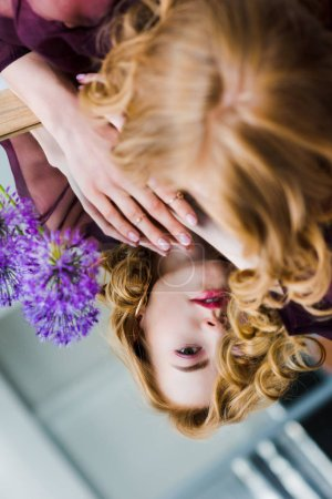 selective focus of young woman looking at reflection while lying on mirror with blue flowers