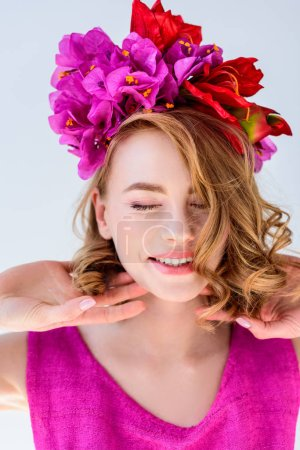 beautiful happy woman with flowers in hair smiling with closed eyes isolated on grey