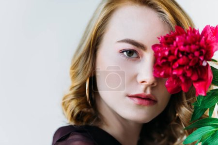 close-up view of girl holding red flower and looking at camera isolated on grey