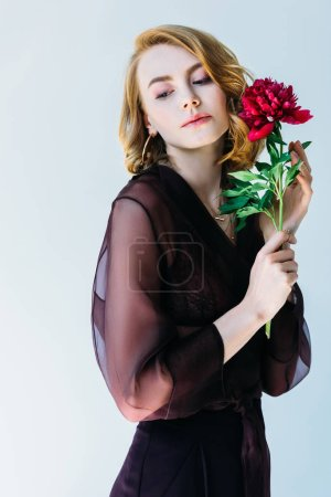 beautiful young woman holding red peony flower and looking away isolated on grey