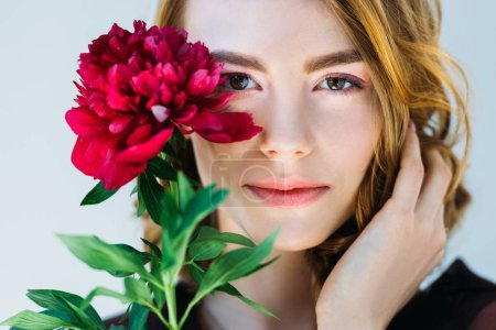 beautiful young woman holding red peony flower and looking at camera isolated on grey