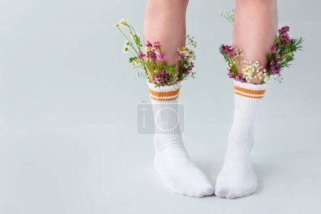 cropped shot of young woman in socks with beautiful flowers standing isolated on grey