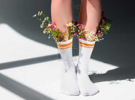 cropped shot of girl with beautiful flowers in socks standing on grey