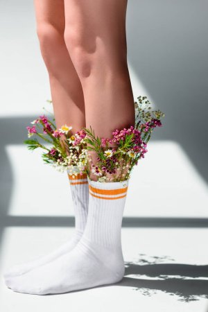 close-up partial view of young woman with beautiful flowers in socks standing on grey