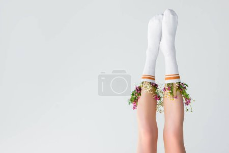 upside down view of female legs with fresh flowers in socks isolated on grey