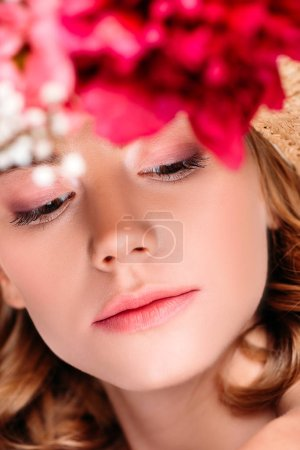selective focus of young woman wearing hat with flowers and looking down