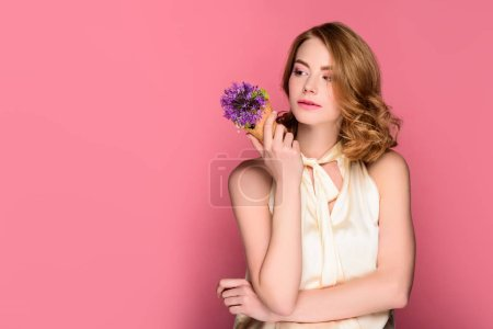 Photo for Pensive girl holding waffle cone with violet flower and looking away isolated on pink - Royalty Free Image