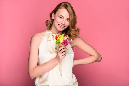 beautiful happy girl holding wafer cone with flowers and smiling at camera isolated on pink