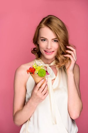 beautiful young woman holding wafer cone with flowers and smiling at camera isolated on pink