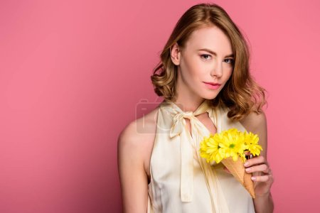 girl holding ice cream cone with yellow flowers and looking at camera isolated on pink