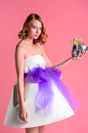 beautiful young woman holding decorative silver skull with flowers and looking at camera isolated on pink