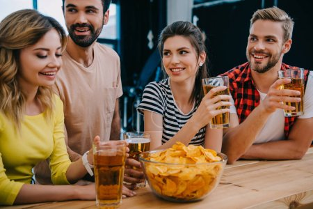 smiling group of friends with beer and bowl of chips sitting at bar counter during watch of soccer match