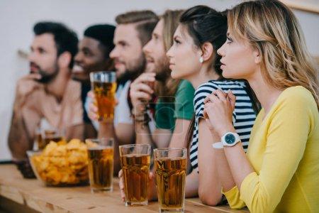 Photo pour Vue du groupe des amis multiculturelles, boire de la bière et regarder football match au bar - image libre de droit