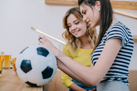Photo for Side view of two smiling female friends watching football match at bar counter with soccer ball and beer - Royalty Free Image