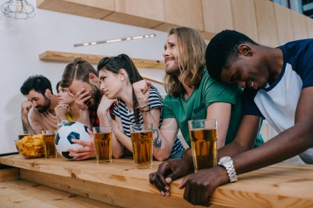 upset multicultural group of friends sitting at bar counter and watching football match