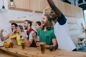 excited multicultural friends celebrating, gesturing by hands and watching football match at bar