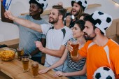 smiling multicultural friends in soccer ball hats celebrating, drinking beer and watching football match at bar