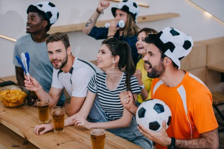 multicultural friends in soccer ball hats celebrating, gesturing by hands and watching football match at bar