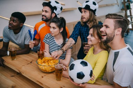 high angle view of smiling multicultural group of friends in soccer ball hats drinking beer and watching football match at bar