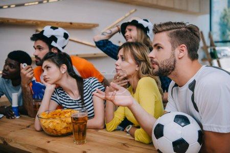 Photo pour Bouleversé les jeunes amis multiculturels dans chapeaux ballon football avec main claquettes et corne fan regarder le football match au bar - image libre de droit